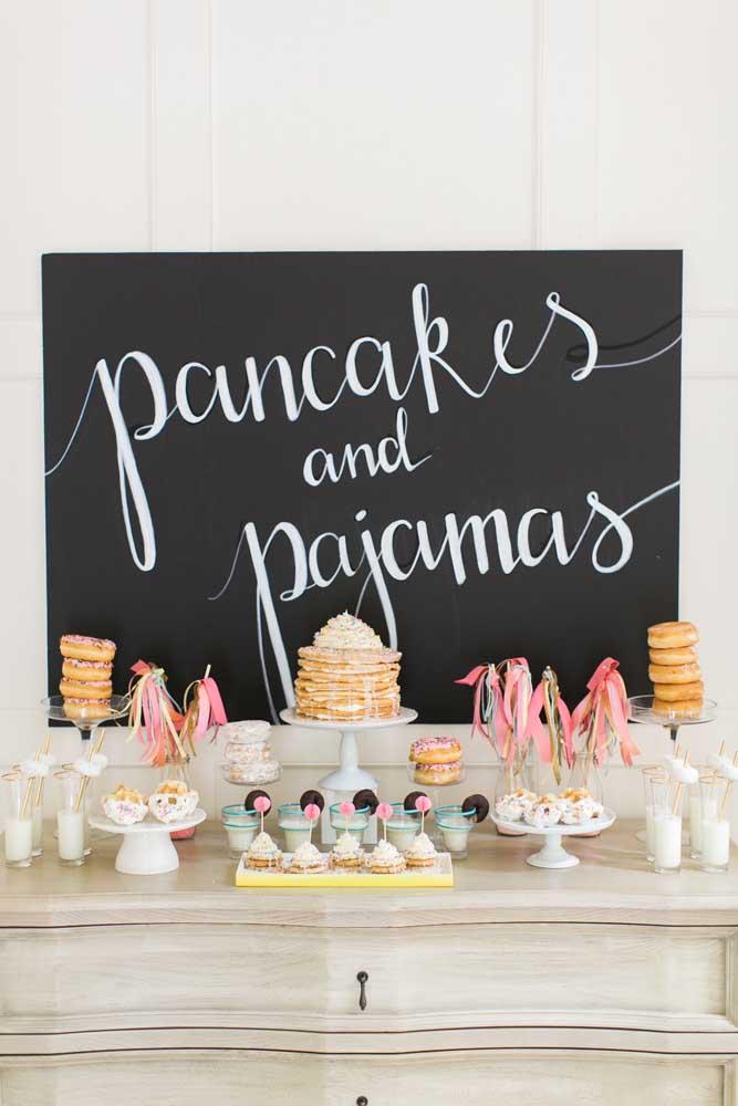 Panquecas, donuts e copos de leite na mesa de guloseimas
