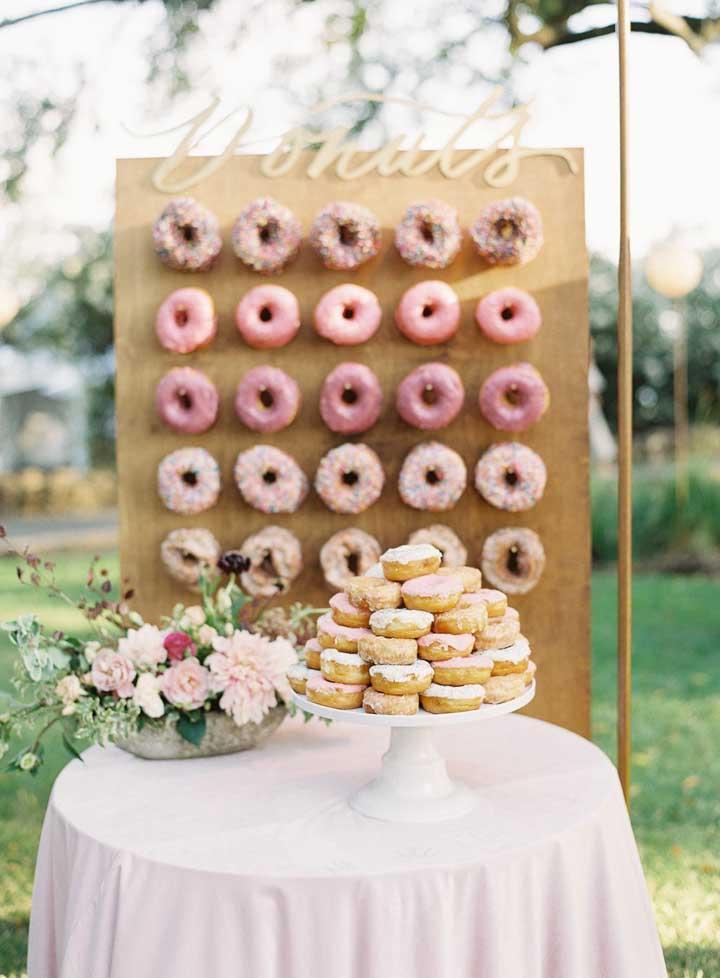A decoração dessa mesa de guloseimas é completada pelo painel de donuts