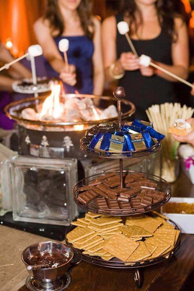Pensou em servir biscoitos na mesa de doces? Repare que logo aos fundos os convidados se divertem com marshmallows na brasa