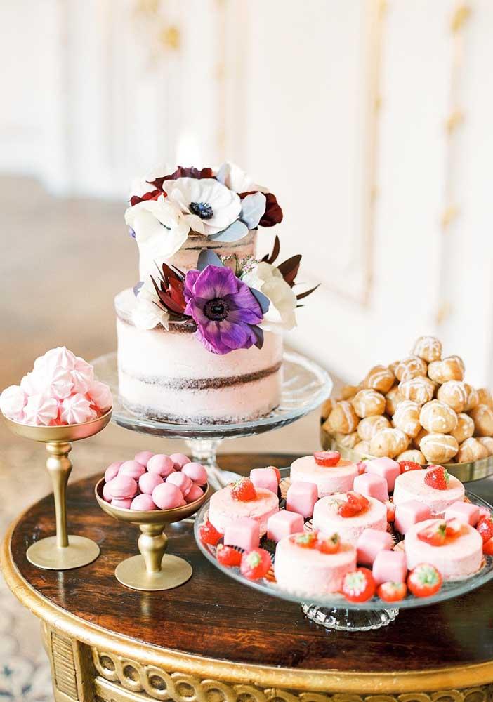 Essa pequena e simples mesa de guloseimas conta com um naked cake decorado com flores e algumas diversidades de docinhos para completar