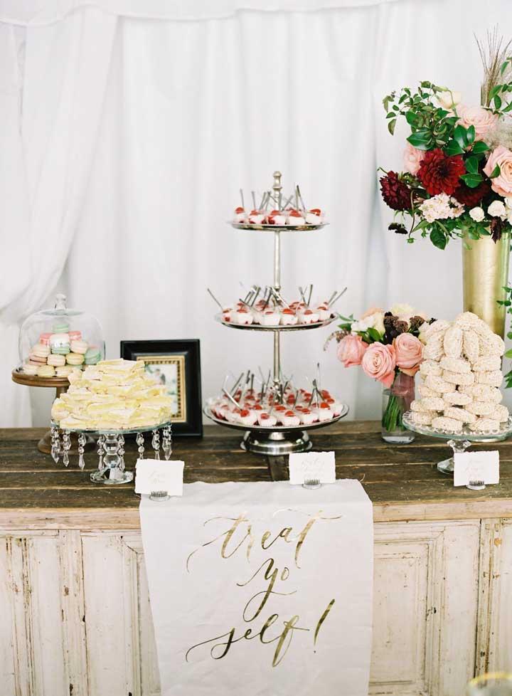Para montar uma mesa de guloseimas rústicas deixe a mesa sem toalha e explore texturas como a da madeira de demolição em contraste com o toque fino das bandejas de doces