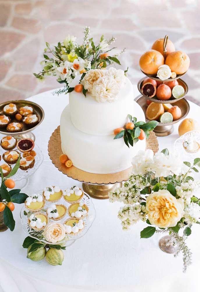 Mesa de bolo de casamento simples e pequena decorada apenas com alguns docinhos, flores e frutas