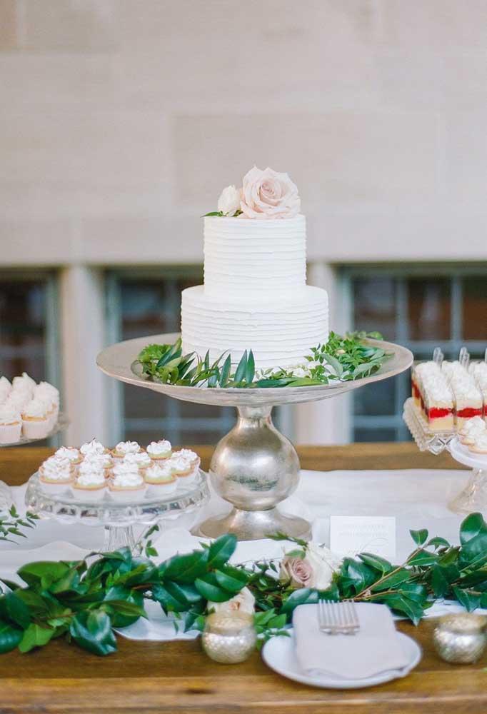 Mesa de bolo de casamento clean. As folhagens garantem um toque moderno à decoração