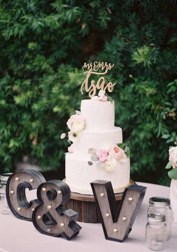 Mesa de bolo de casamento moderna com as iniciais dos noivos em um letreiro luminoso