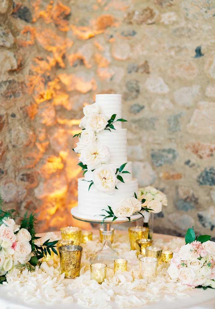 Mesa de bolo de casamento com bolo de quatro andares. Destaque para as pétalas de rosas espalhadas pela toalha