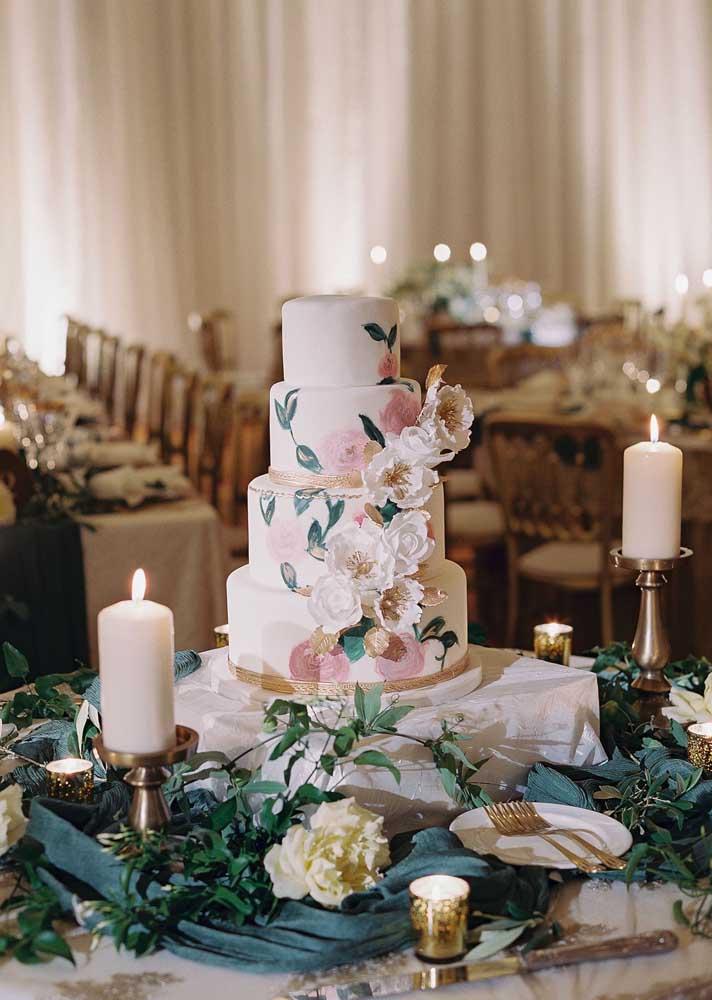 Mesa de bolo de casamento posicionada no centro do salão