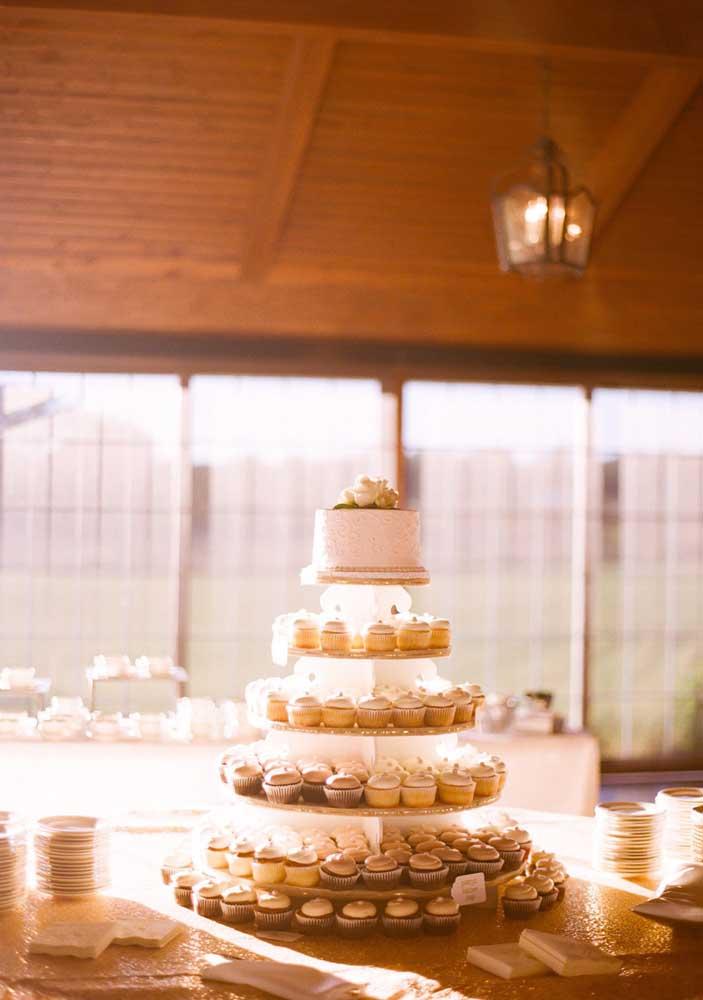 Já aqui nessa mesa o que se destaca não é o bolo, mas a torre de cupcakes em formato de bolo