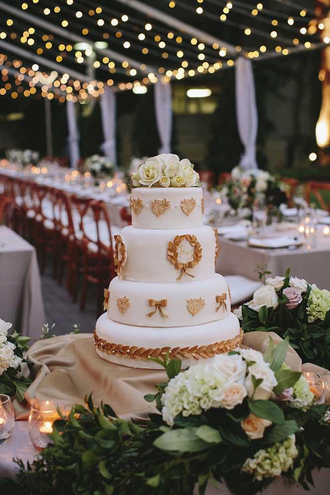Mesa de bolo de casamento posicionada ao fundo do salão, mas de frente para a entrada