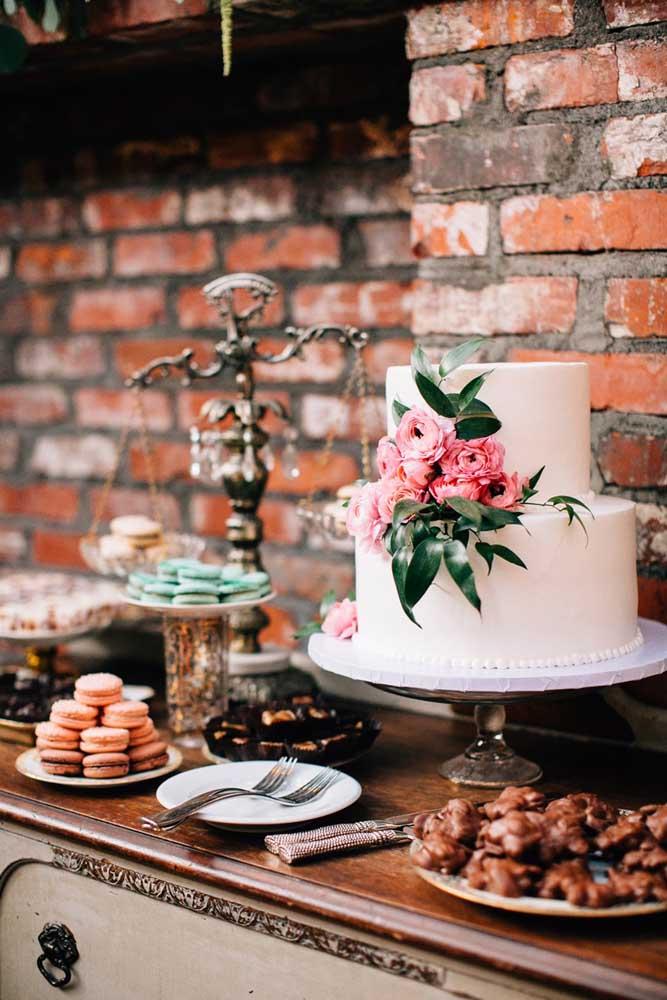 A parede de tijolinhos aparentes garantiu um charme rústico super interessante para a mesa do bolo