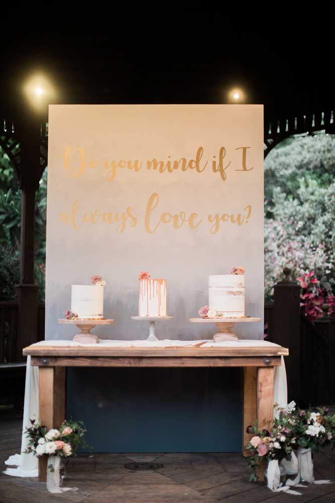 O charme dessa mesa de bolo de casamento é o painel com a frase romântica