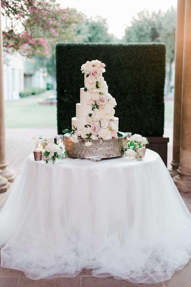 Mesa de bolo de casamento clássica. Destaque para a toalha que lembra um véu de noiva