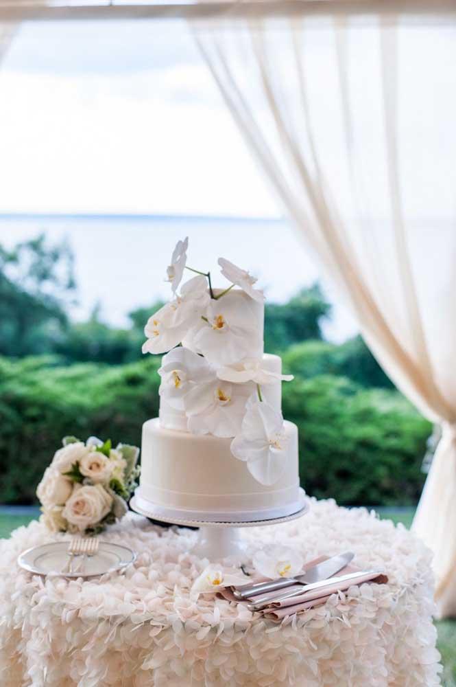 O destaque dessa mesa de bolo de casamento é a toalha com detalhes de pétalas de flores