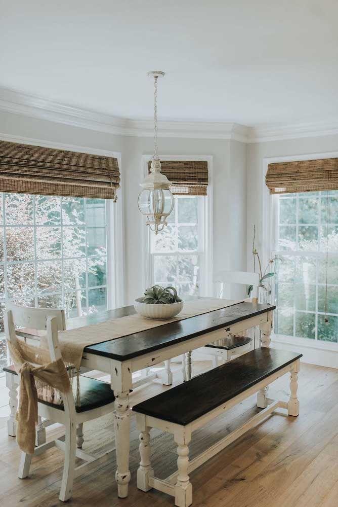 As grandes janelas de vidro dessa sala de jantar receberam cortinas de bambu no tamanho adequado a cada uma delas