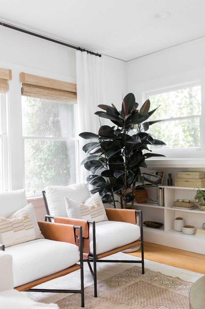 A sala branca cheia de janelas apostou no uso das cortinas de bambu sobrepostas à cortina de pano