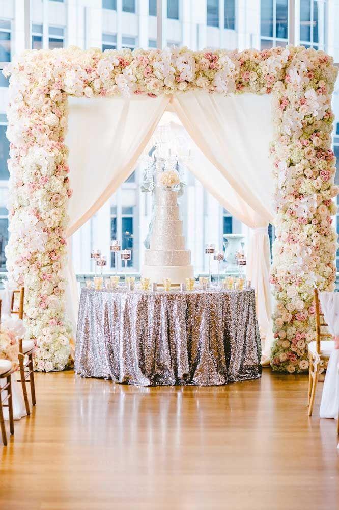 O arco de flores é a moldura perfeita para esse bolo prata de seis andares.
