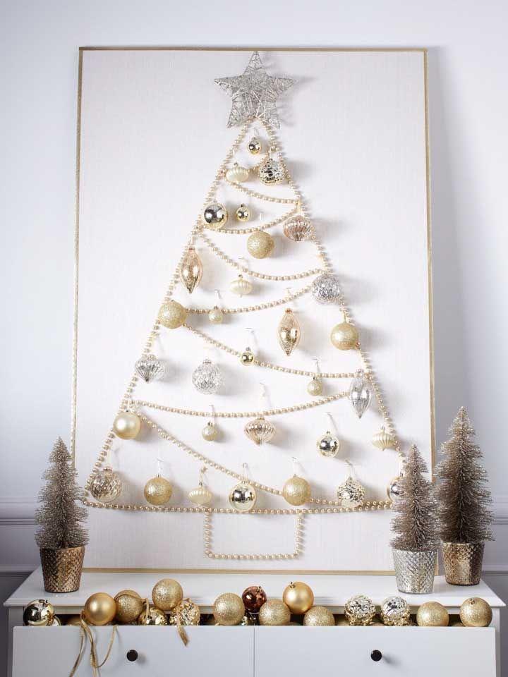 As bolinhas douradas garantem o glamour dessa árvore de Natal de parede