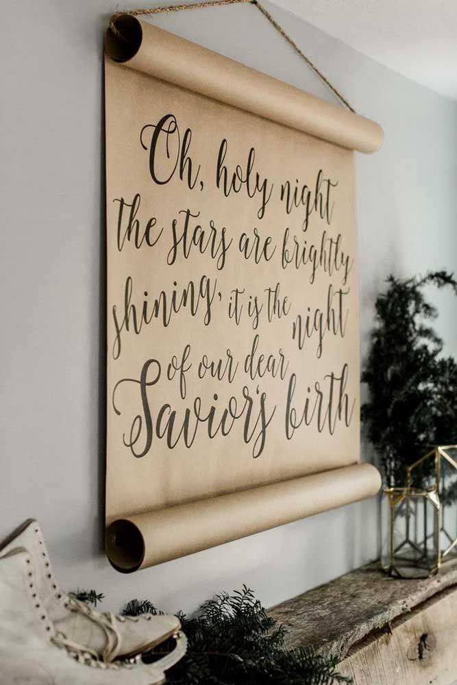 O rolo de papel cartão pendurado na parede traz a mensagem de natal; uma ideia simples e barata de painel