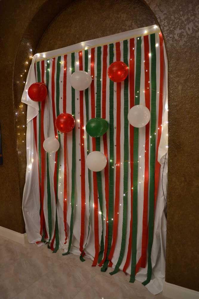 Painel de Natal feito com papel crepom e bexigas; use as cores do Natal para deixar o enfeite mais temático