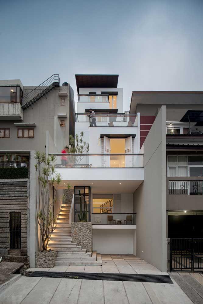O grande destaque dessa frente de casa é a escada que se abre na altura da rua; o uso das pedras e do vidro também não passa despercebido