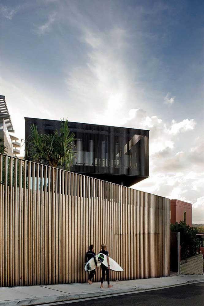 O muro de madeira contrasta com a fachada de metal no mesmo desenho