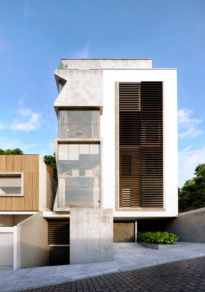 Os cortes garantem uma forma geométrica diferenciada para frente da casa; para o acabamento foram escolhidos o concreto aparente, o vidro e um toque discreto de madeira