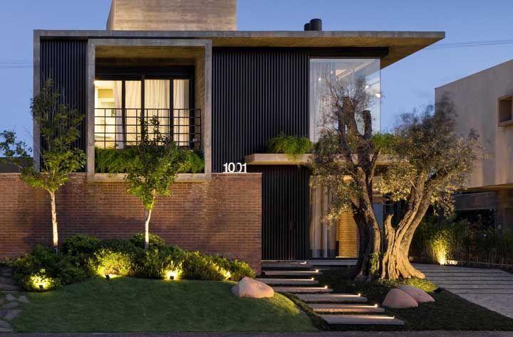 A frente dessa casa apostou na rusticidade do tijolinho combinado a um jardim bem iluminado