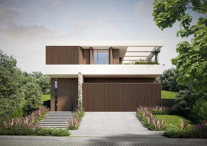 Emoldurada pela natureza, a frente dessa casa conta apenas com madeira e uma pintura branca simples