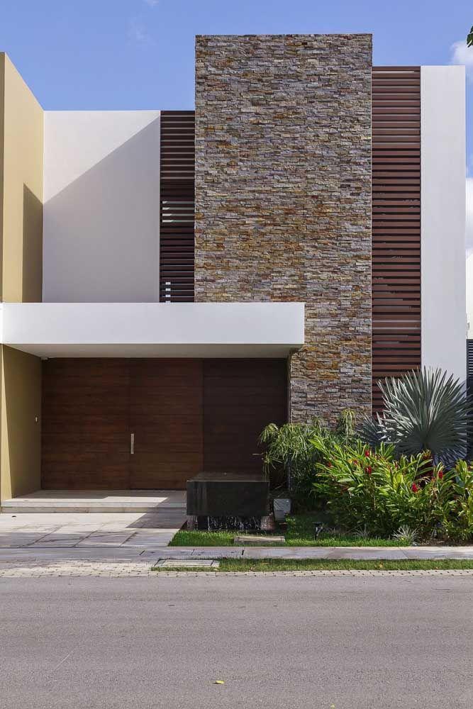 As pedras criam volume na parte central da casa; o acabamento restante fica por conta da pintura