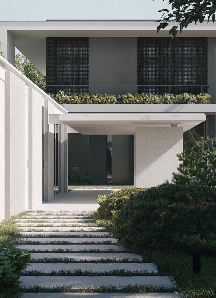 A frente de casa branca e de linhas retas ganhou o contorno verde das folhagens ao redor