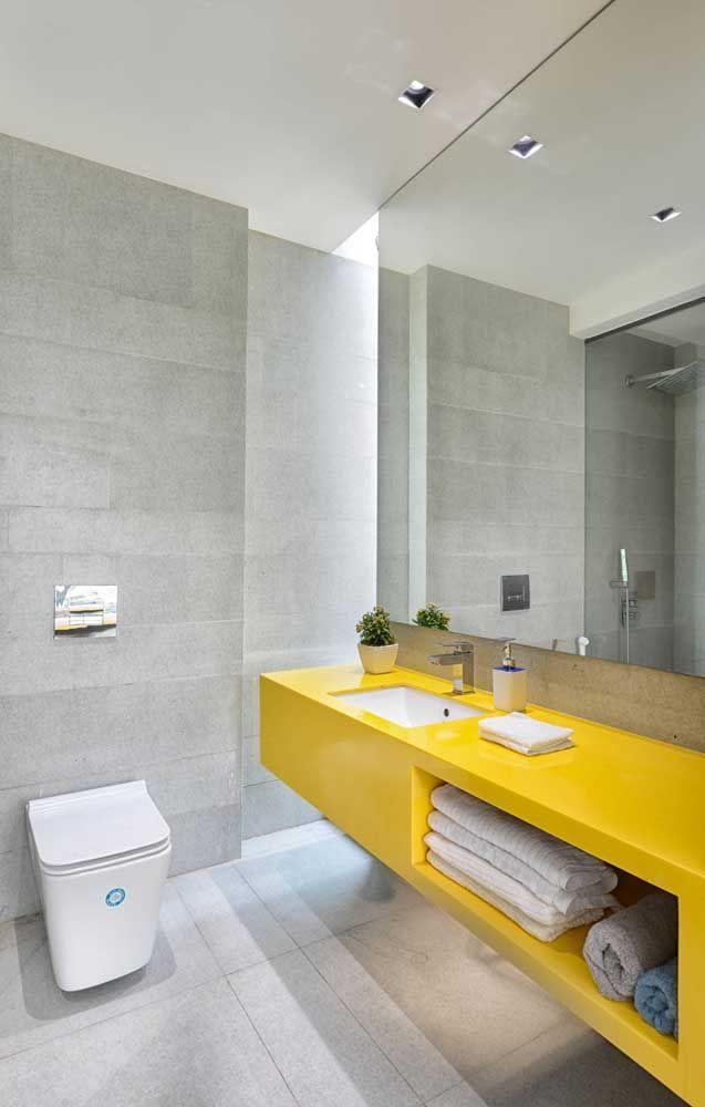 Bancada amarela trouxe contraste e vida para o banheiro de fundo cinza