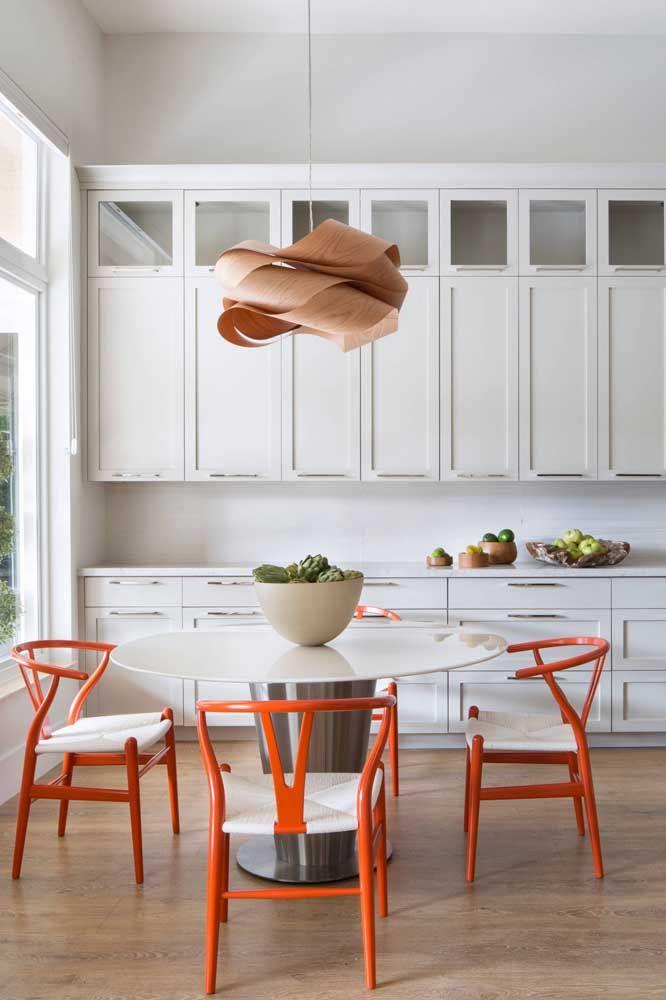 Já a cozinha branca soube como tirar proveito das cadeiras laranjas