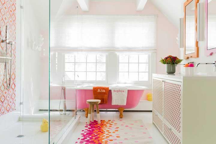 Banheiro branco, mas dinâmico e cheio de vida, graças a combinação marcante entre laranja e rosa