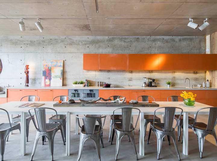 Sobre a parede de concreto aparente armários laranjas