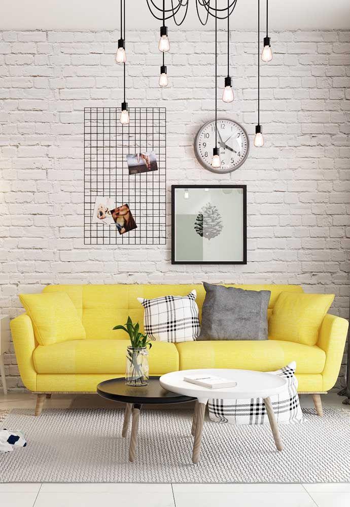 Em meio a sala branca, o sofá amarelo é puro contraste e enche o ambiente de alegria