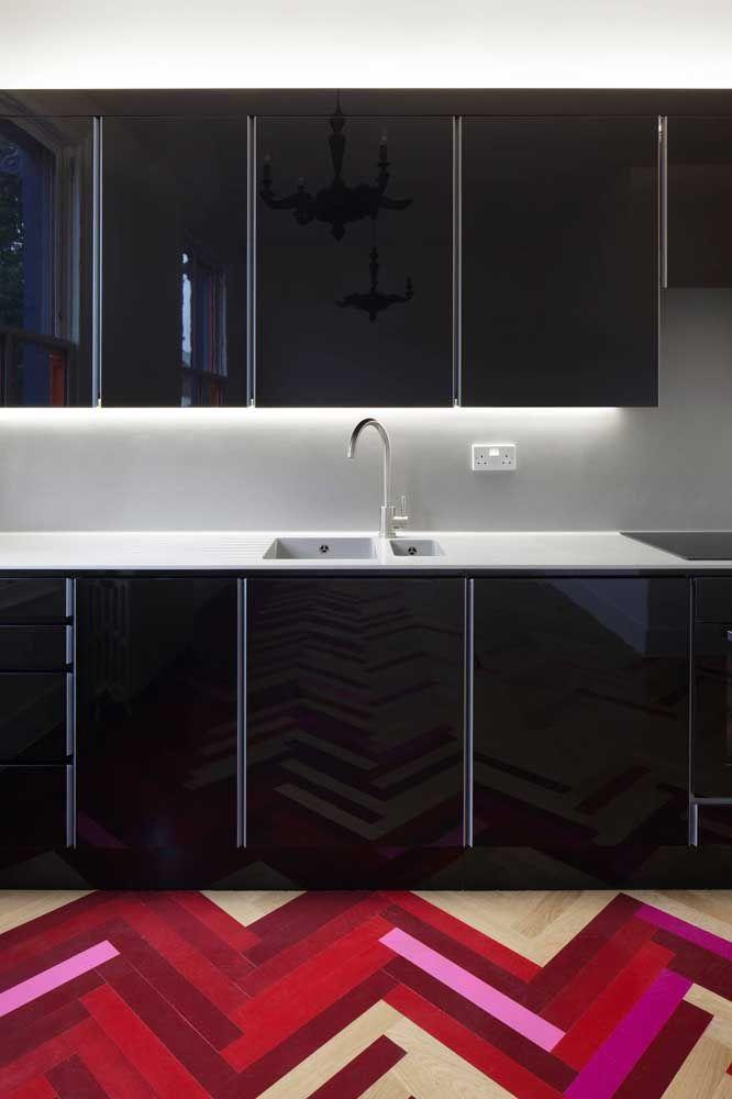 A cozinha preta apostou e teve sucesso com o piso de tons vermelho e rosa; as cores trouxeram alegria e descontração