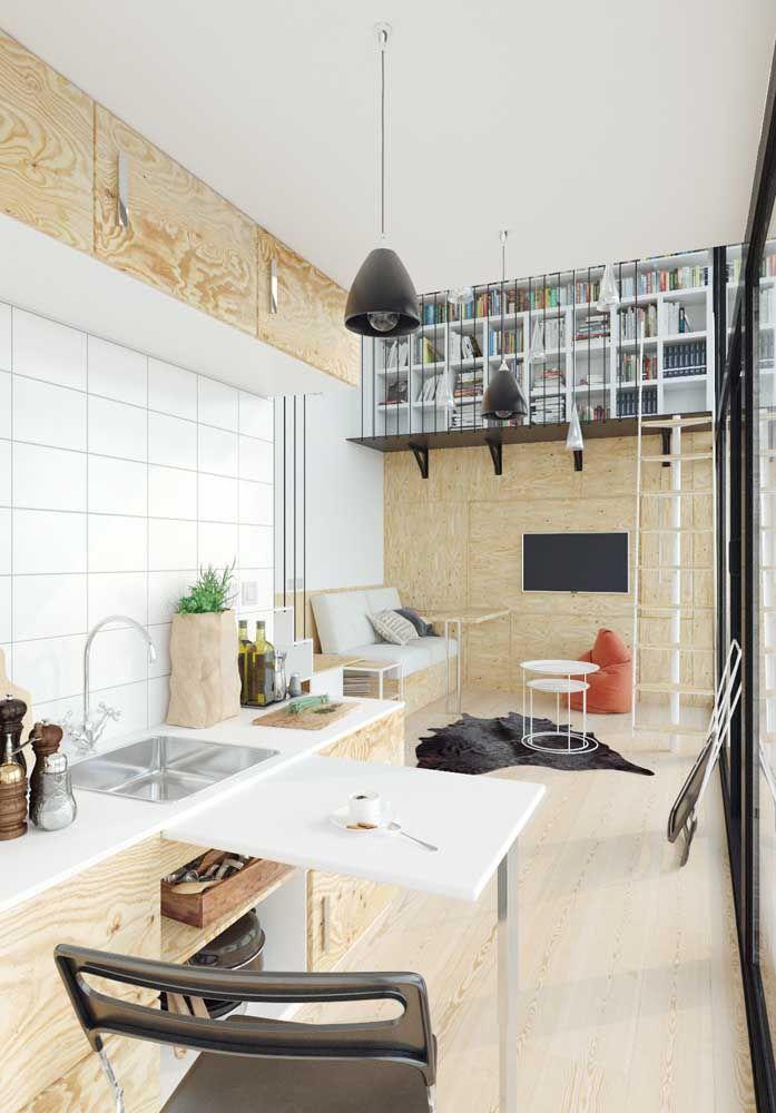Apartamento de soluções práticas: bancada para preparo dos alimentos, biblioteca suspensa e armários aéreos