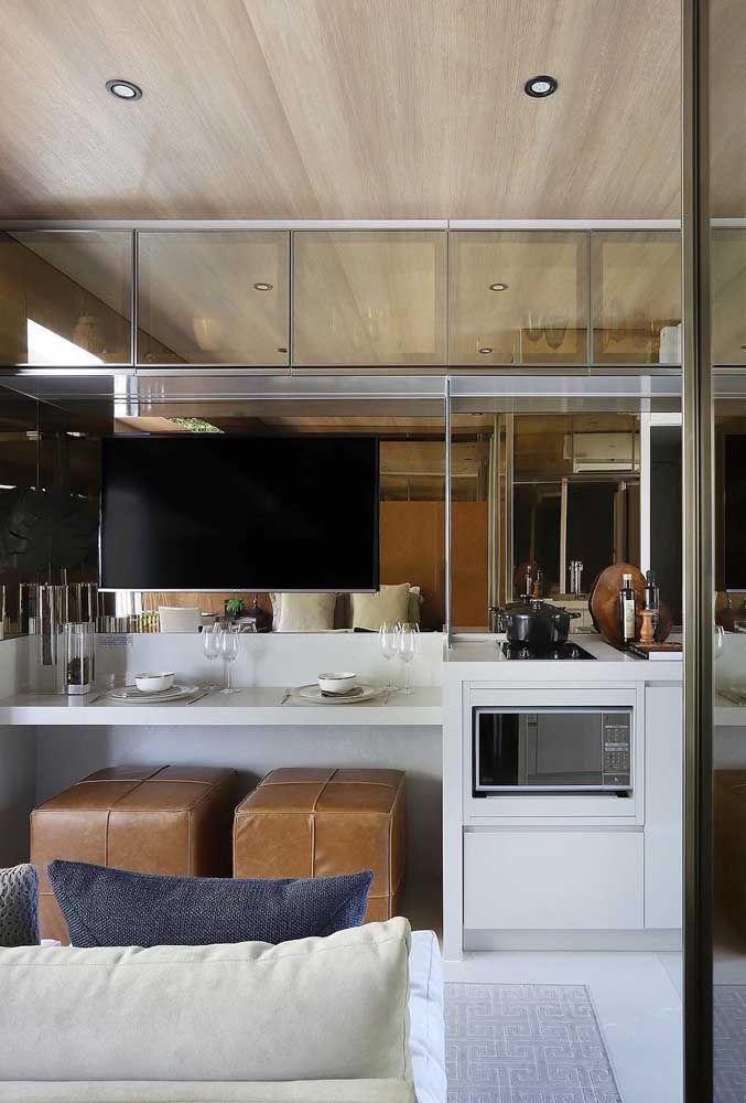 Banquetas sob o balcão que serve de rack e bancada de refeição, além de muitos espelhos nos móveis para ampliar o espaço