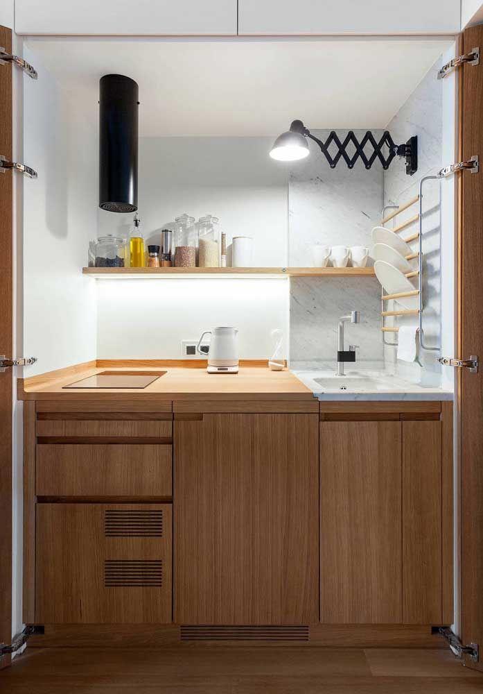 A cozinha pequena foi salva pelo uso das prateleiras e suportes de parede; o móvel com múltiplas repartições também ajuda a organizar a rotina