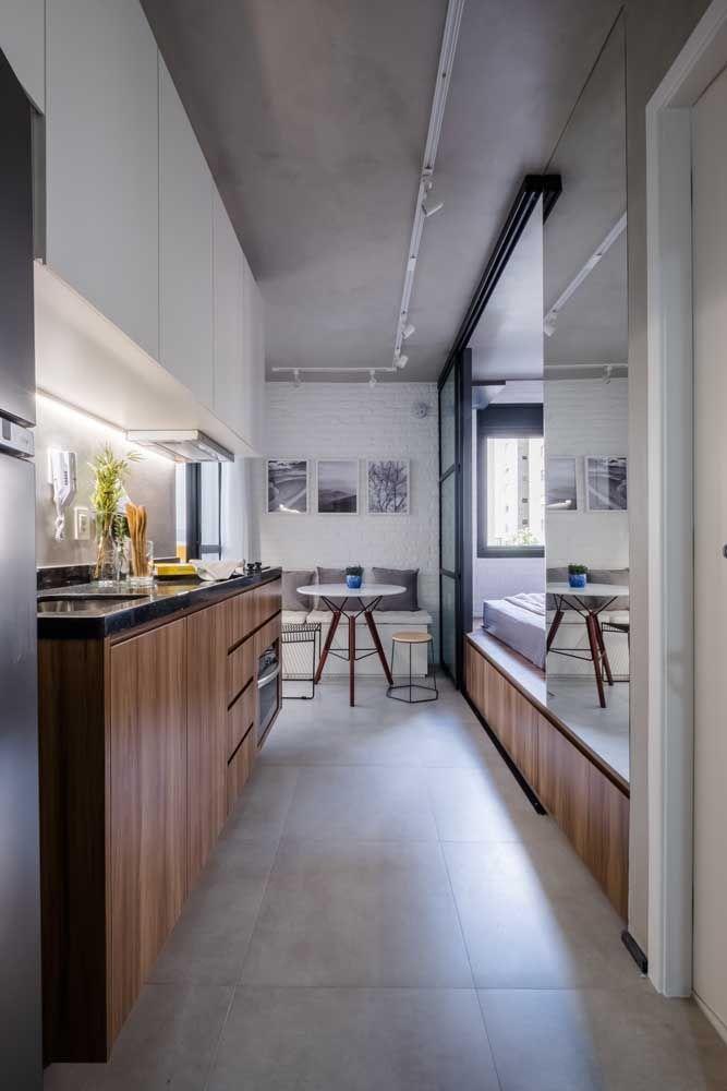 O degrau entre a cozinha e o quarto foi aproveitado como armário nesse apartamento