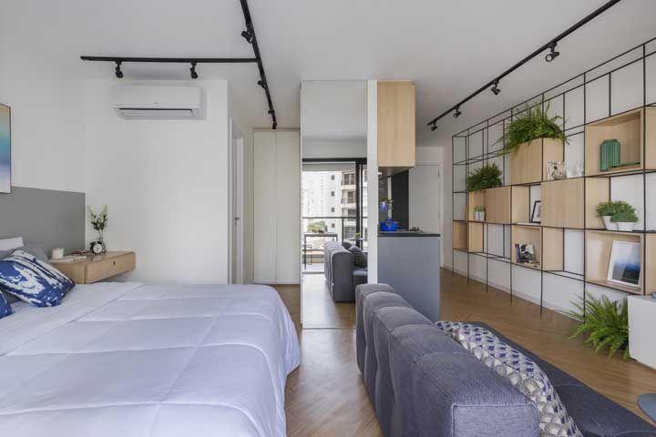 Nesse apartamento, os móveis pertencem ao mesmo ambiente e a estante de nichos liga toda a extensão do apartamento