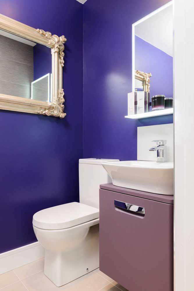 Azul quase roxo ou um roxo quase azul? O fato é que a cor trouxe um ar de glamour e requinte ao banheiro, especialmente pelo uso da moldura dourada