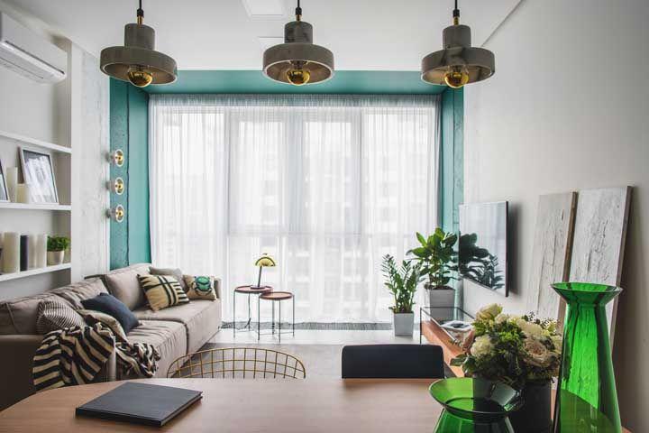 A sala branca foi emoldurada pela faixa de parede azul; para criar outro ponto de destaque foram inseridos dois vasos de vidro verde sobre a mesa