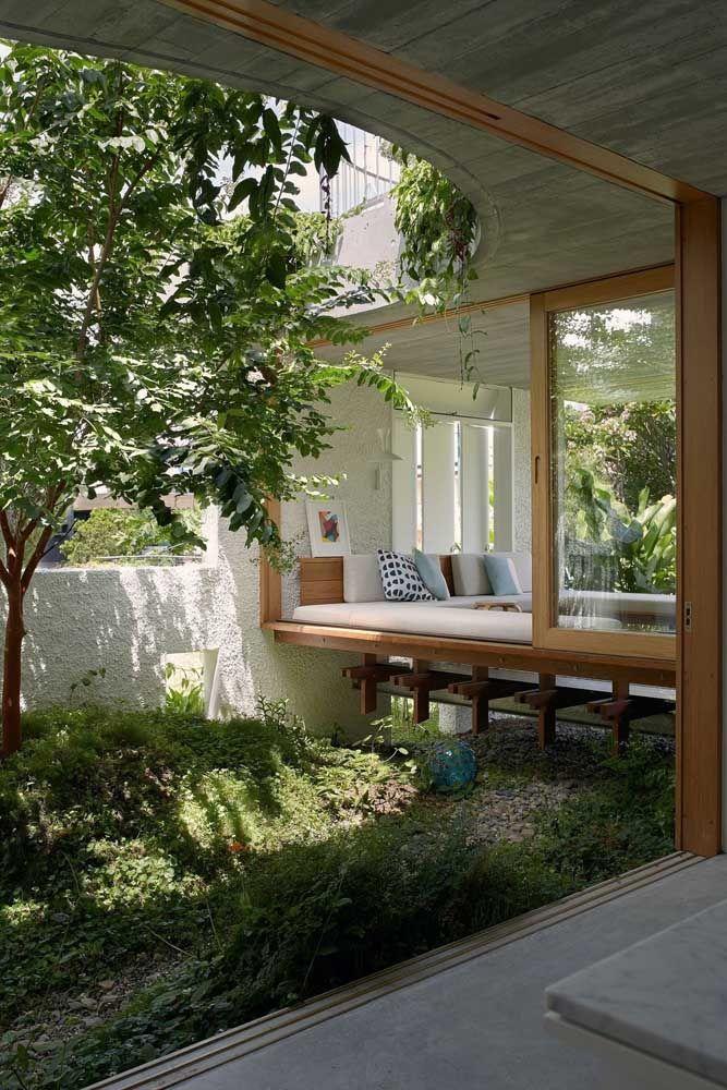 O sofazinho apoiado na janela torna o jardim de inverno uma experiência ainda mais aconchegante