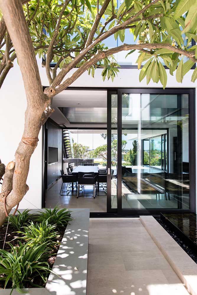 A árvore já crescidinha garante sombra e frescor para entrada da casa; destaque para o pequeno lago de pedras ao lado