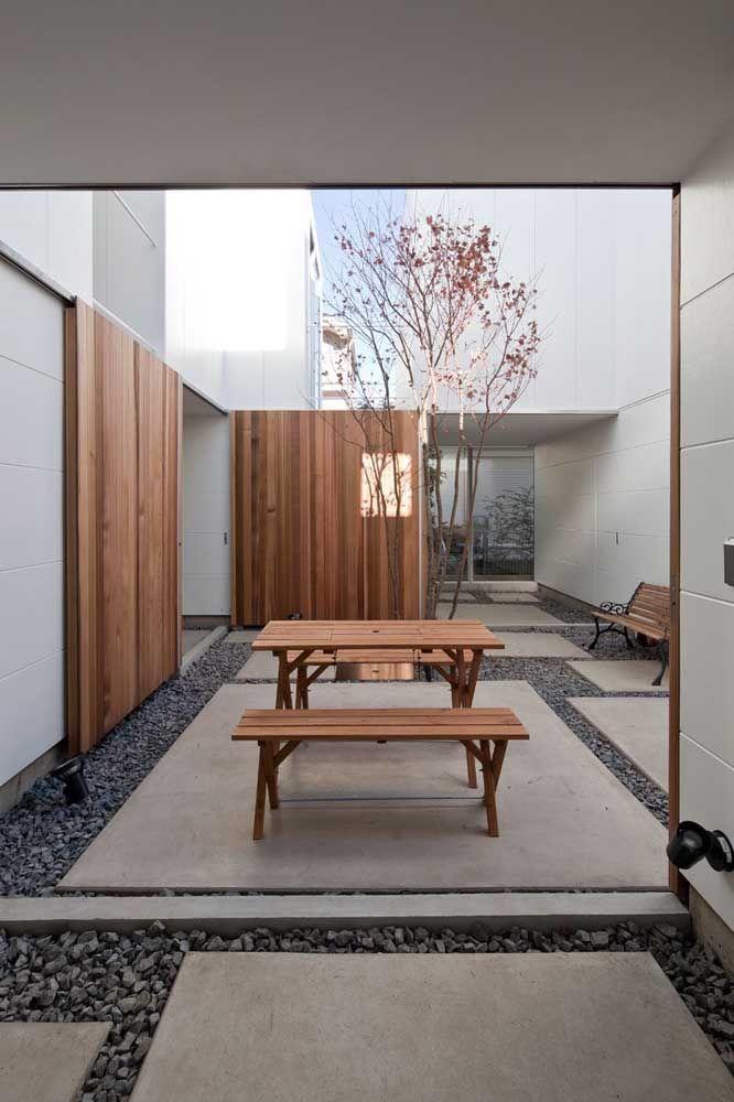 Os bancos de madeira permitem aproveitar ao máximo o jardim de inverno que, nesse caso, foi feito apenas com pedras e uma pequena árvore