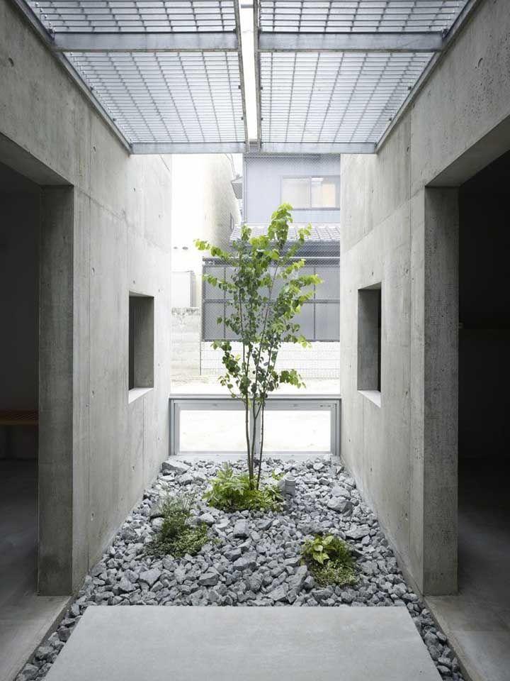 A casa de concreto aparente apostou em um jardim de inverno cheio de pedras