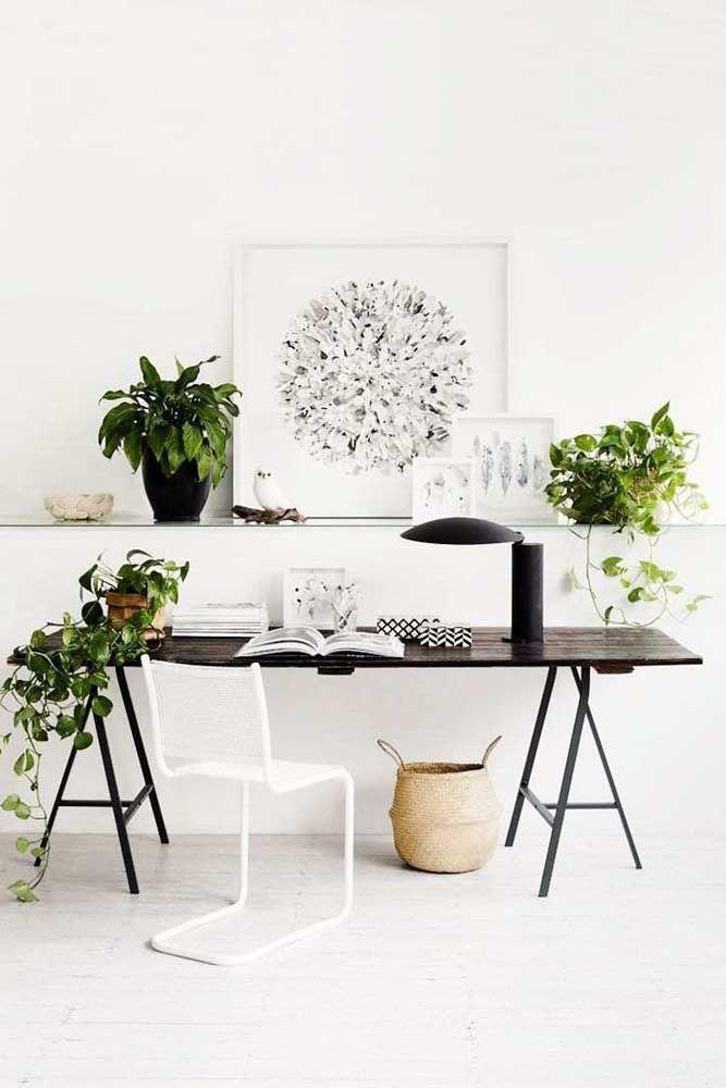 O escritório branco apostou no verde intenso das folhas da jiboia para criar contraste e trazer vida e alegria ao ambiente