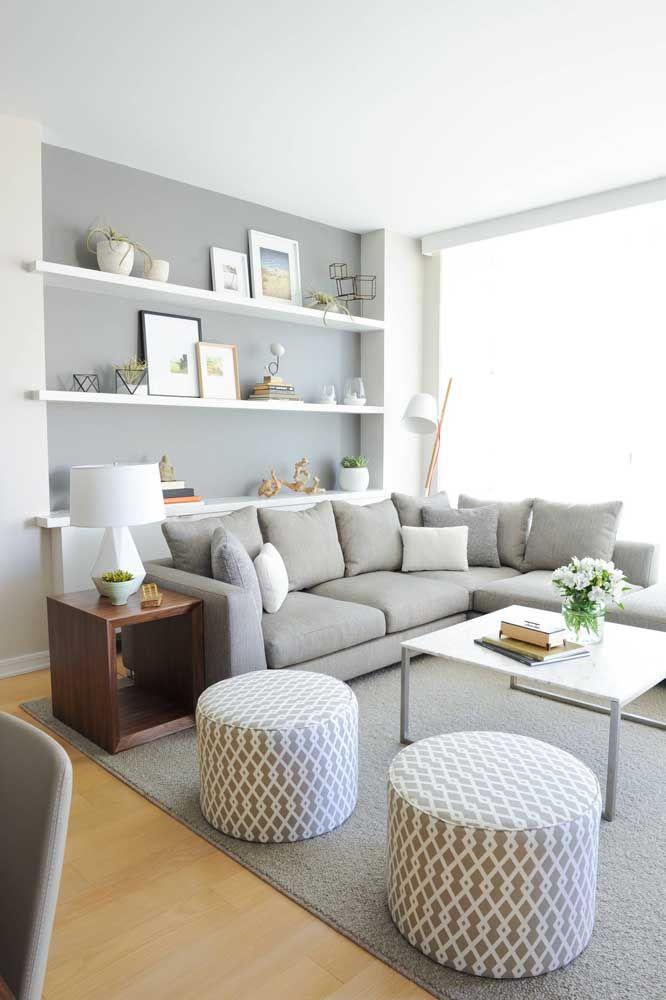 A dupla de puffs redondos ajuda a delimitar o espaço da sala