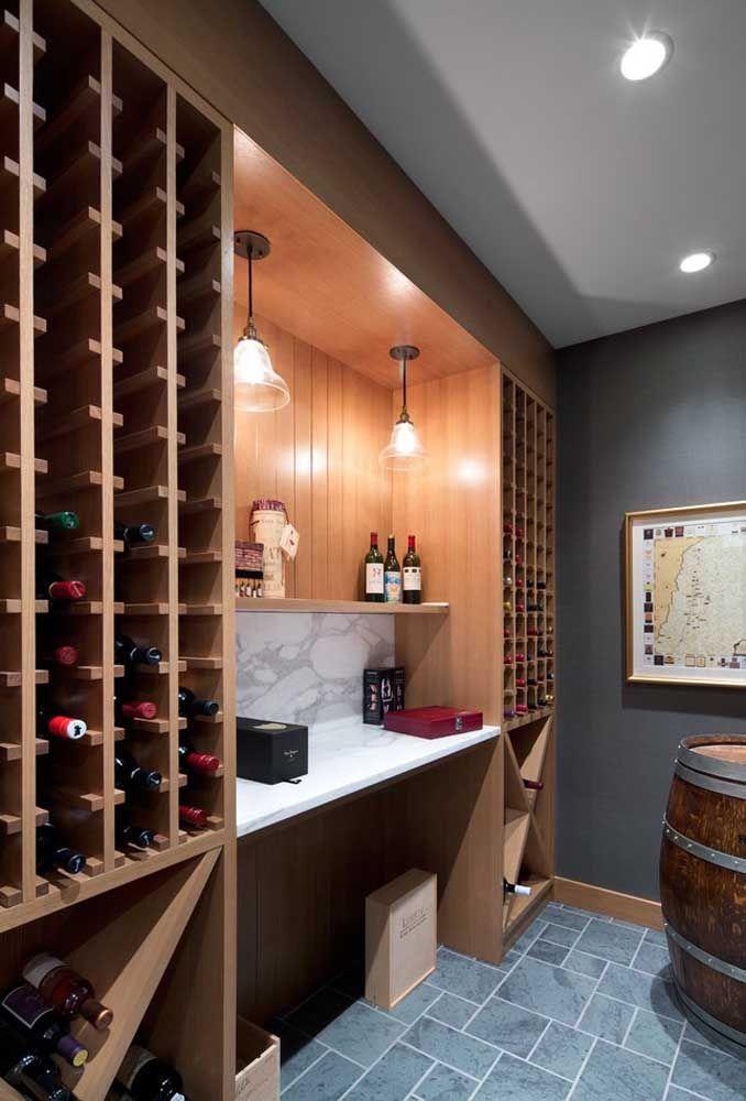 As garrafas preenchem a lateral do móvel em um nicho dedicado só para elas; para completar a decoração do ambiente, um antigo barril de vinho