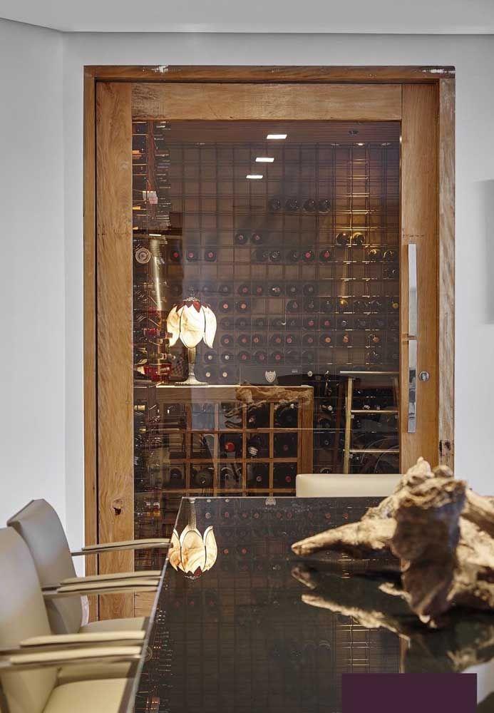 A sala de jantar ficou mais valorizada com essa adega de madeira que se estende do chão até o teto